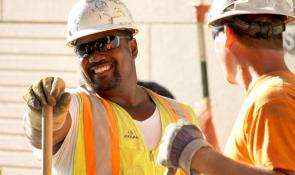 Two construction workers in hard hats smiling.