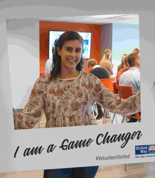 Woman behind a large polaroid frame with the words I am a game changer.